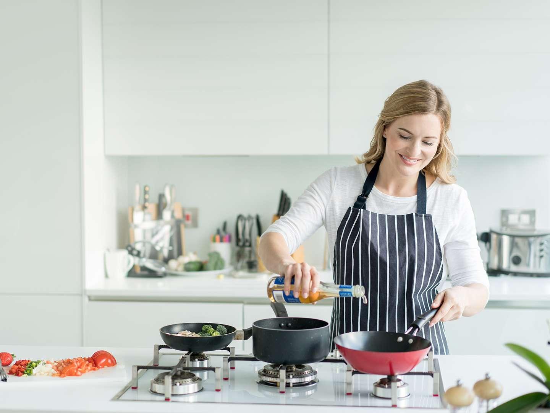 Frau kocht mit Öl in der Küche